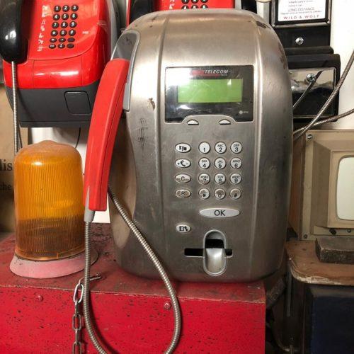 Telefono pubblico argentato e rosso moderno